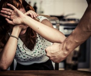 Woman covering face in fear of abuse