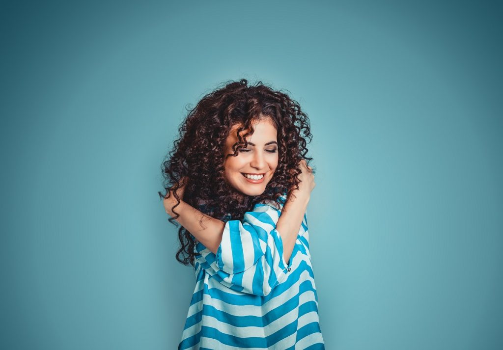 Woman with curly hair hugging herself