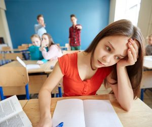 Young girl suffering from bullying in the classroom