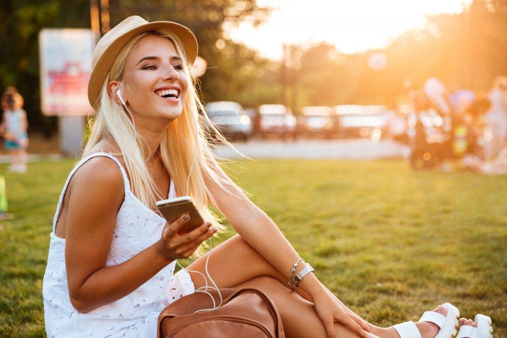 teen enjoying music at the park