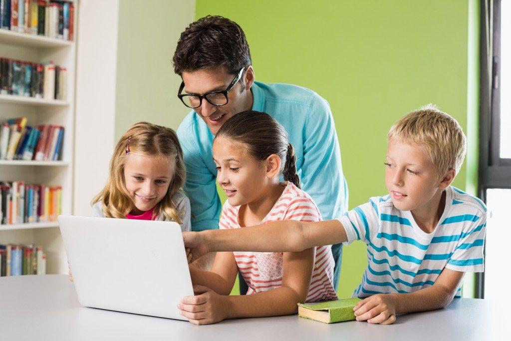 man teaching three toddlers