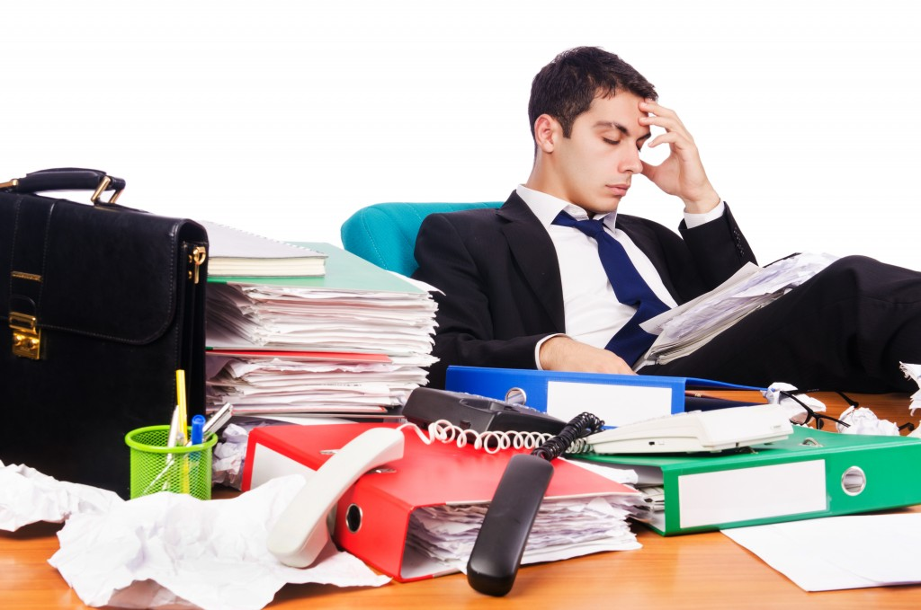 businessman at his desk stressed about clutter