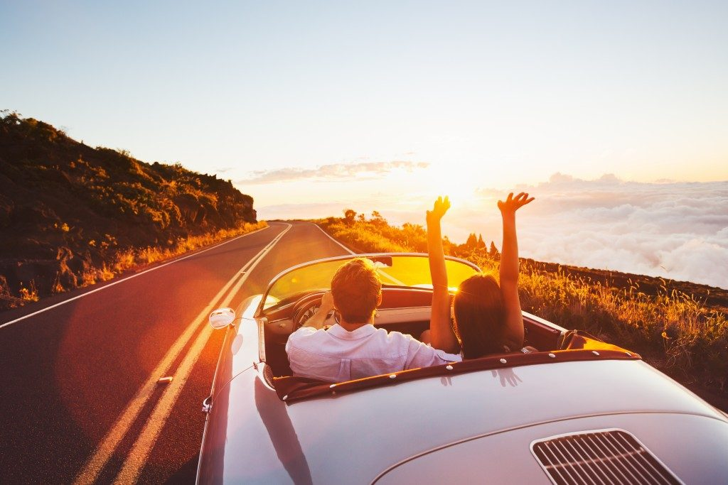 Couple driving on country road with sunset