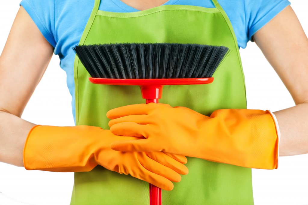 holding a broom with gloves and wearing an apron