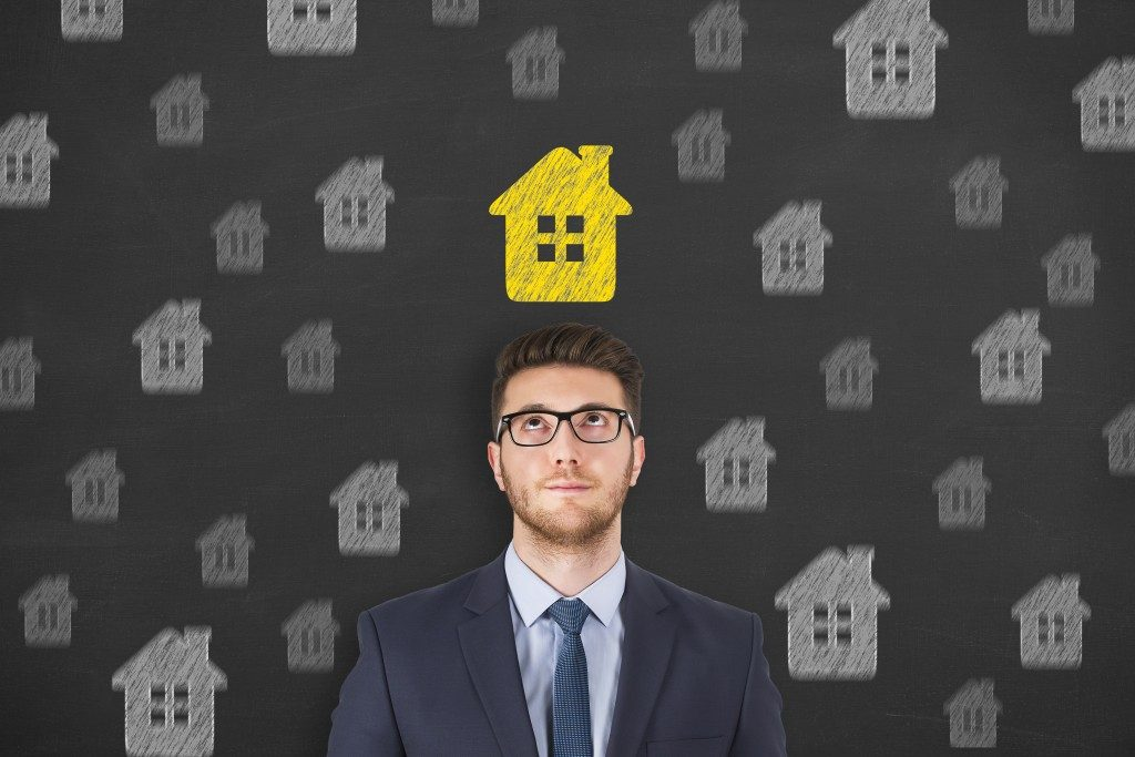man with a drawing of a yellow house above him
