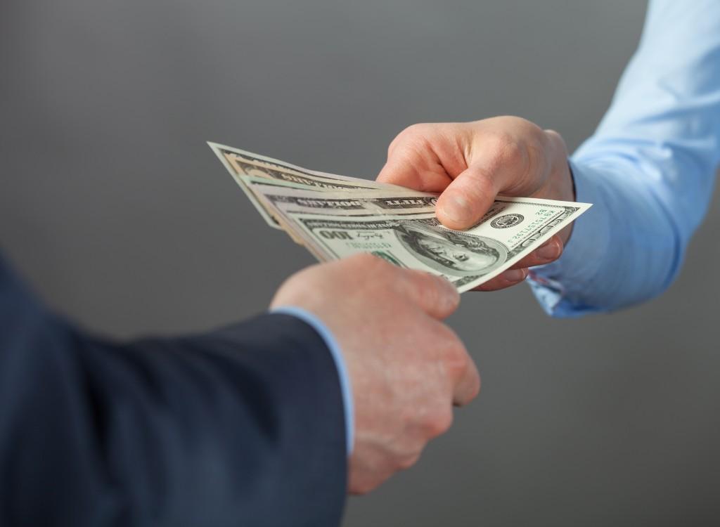 Man handing another man money