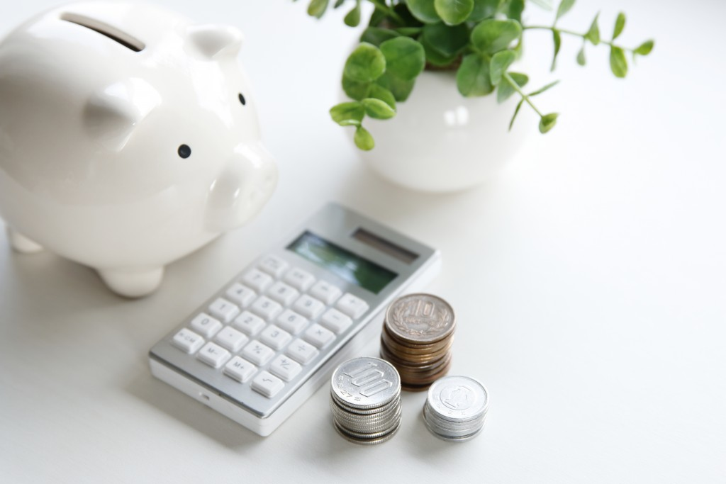 a white piggy bank, white calculator, and coins on top of a white table