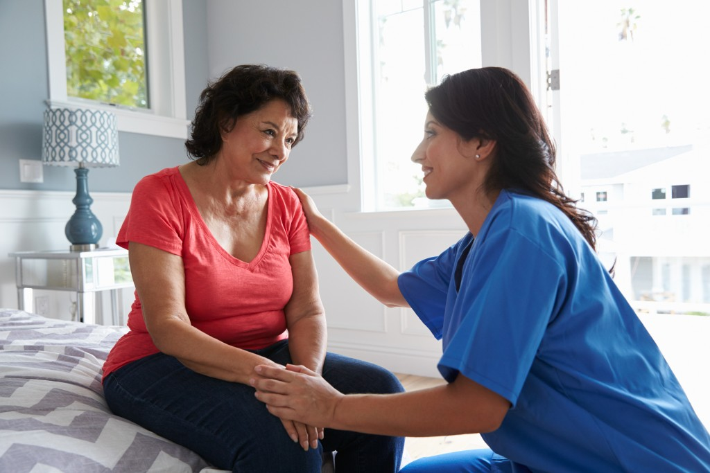 Caregiver comforting a female patient with dementia