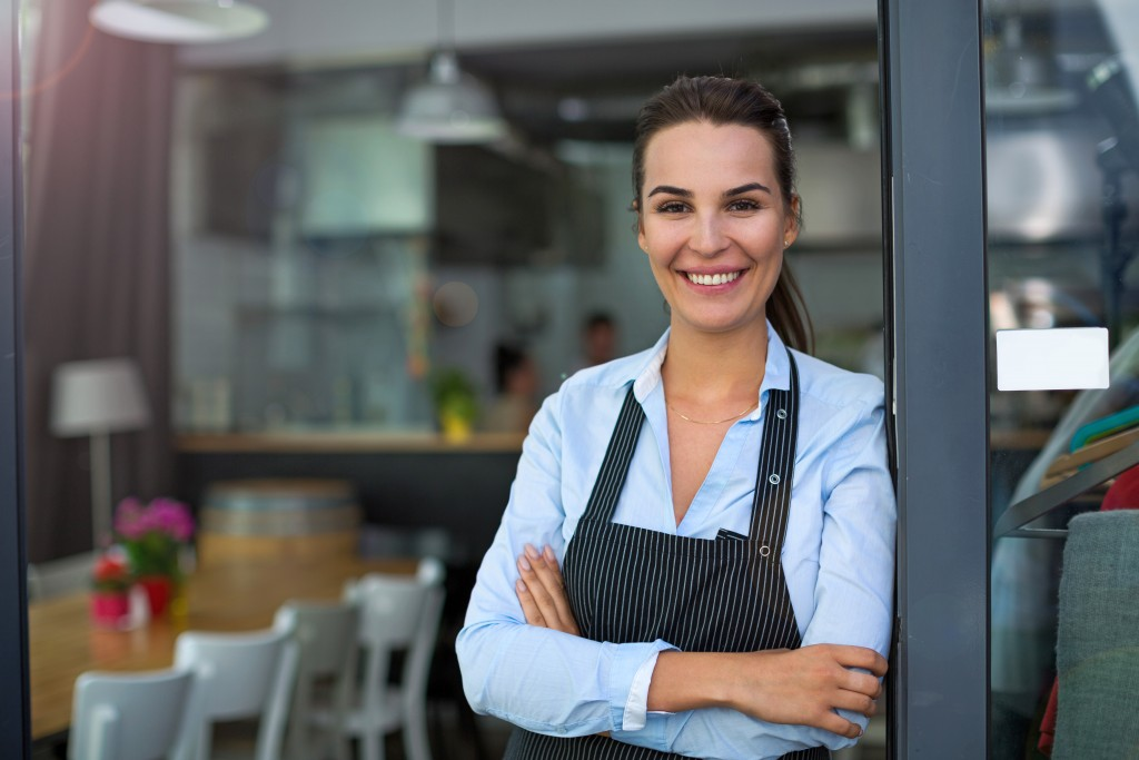 smiling restaurant owner beside the door