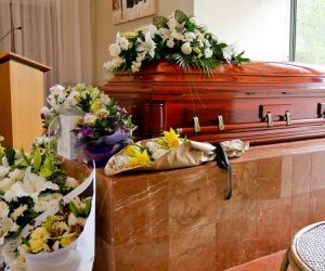 coffin with flowers around it