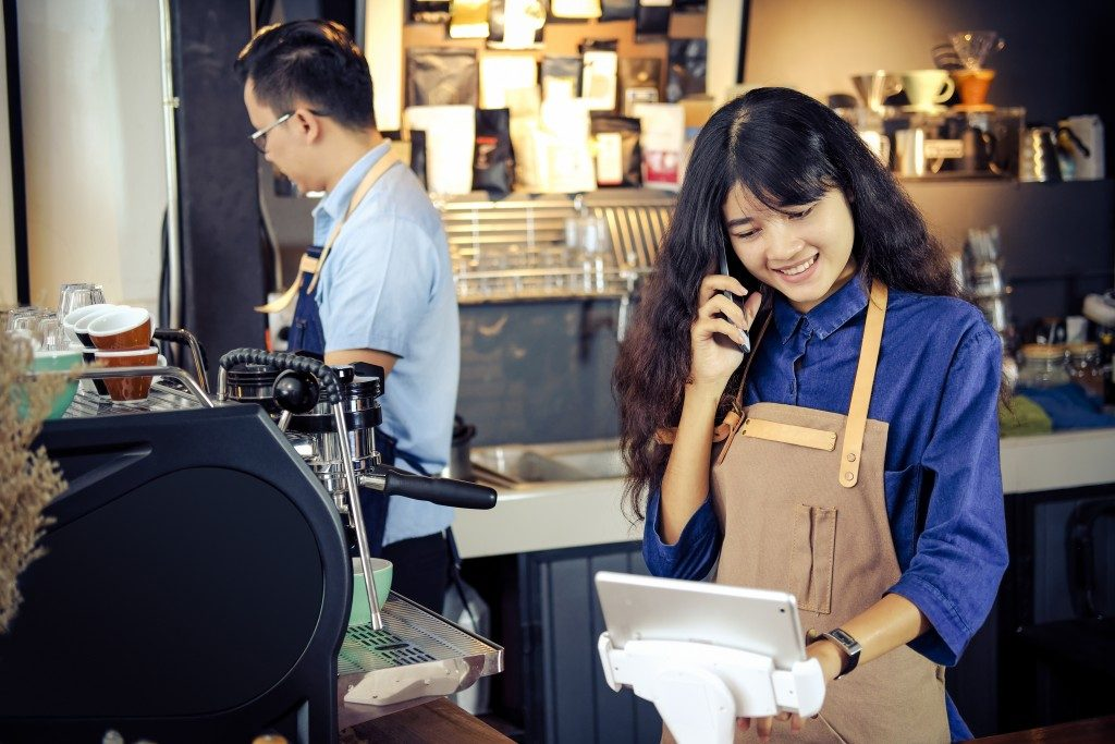 Asian barista talking order by phone in her shop.