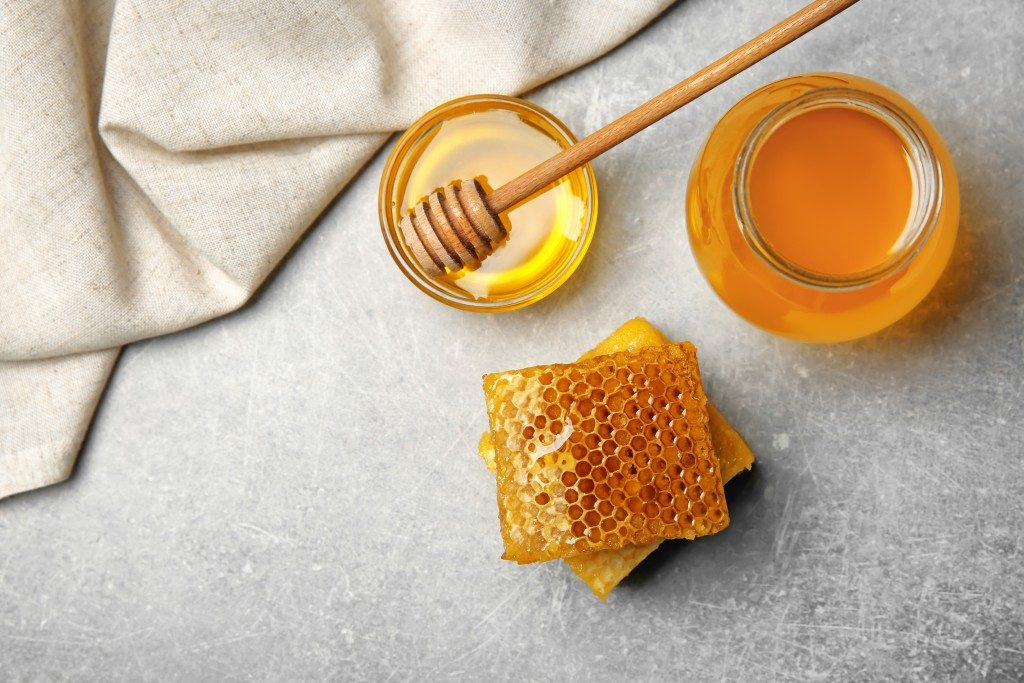 Delicious honey and fresh honeycombs on table