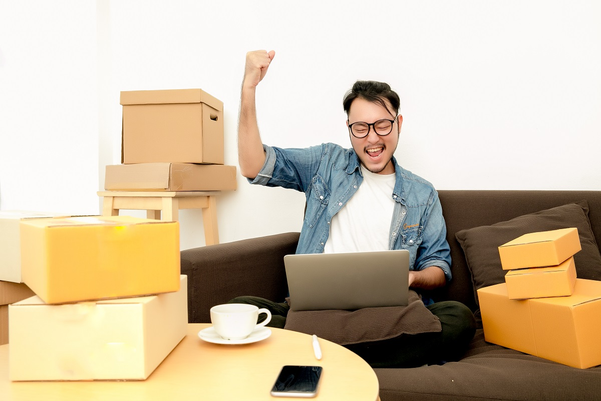 man sitting on the couch happily raising his hand while looking at his laptop
