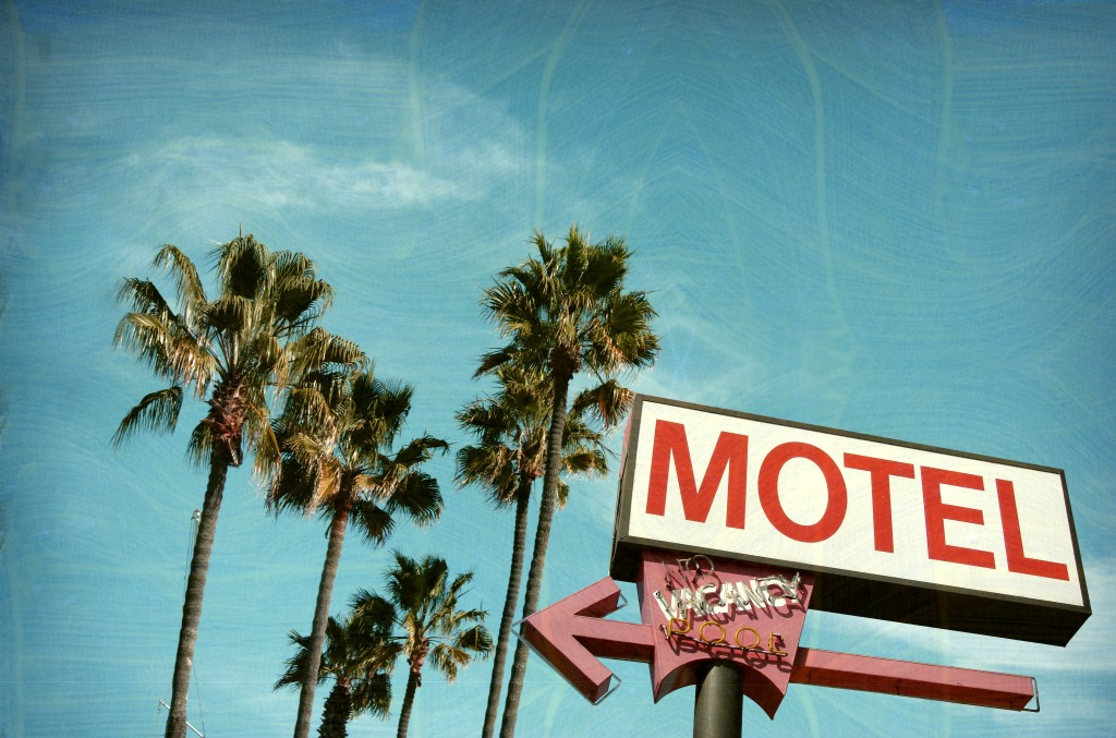 aged and worn vintage photo of motel sign palm trees