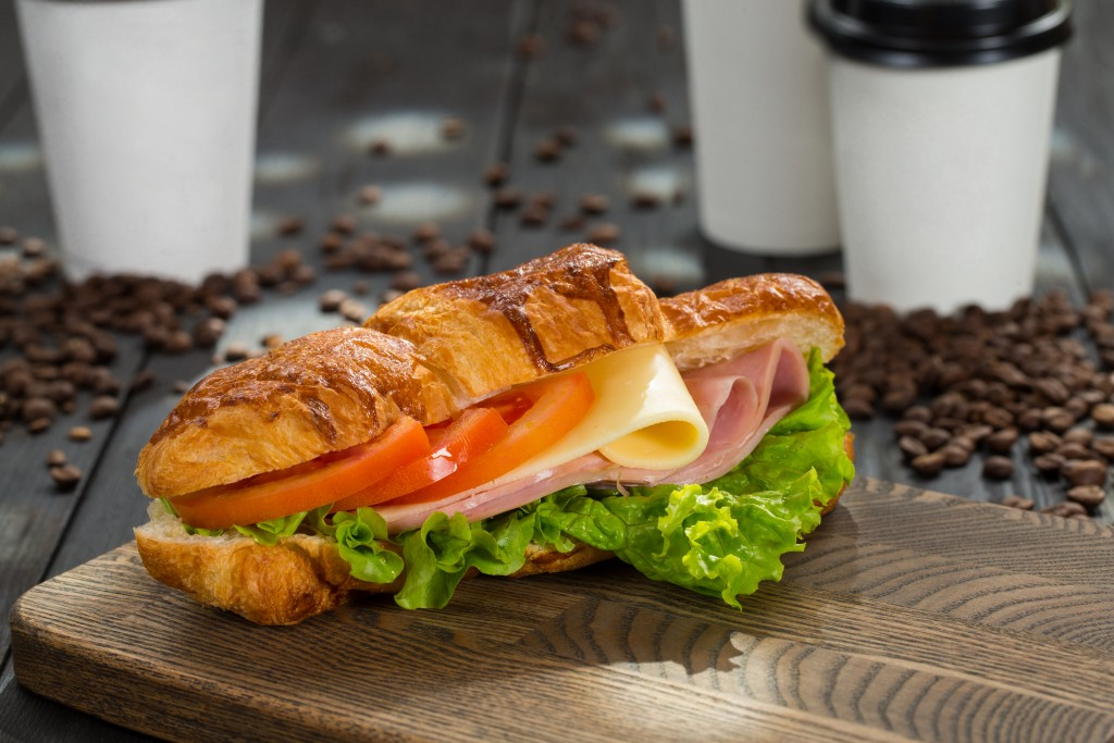 sandwich with ham, cheese, tomatoes and lettuce on a cutting board