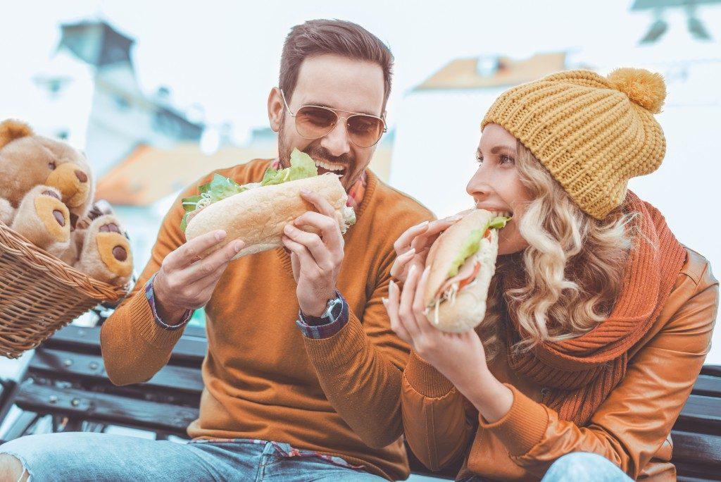 pair eating sandwiches