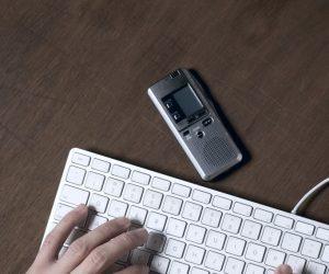 Journalist's hands transcribing audio into text