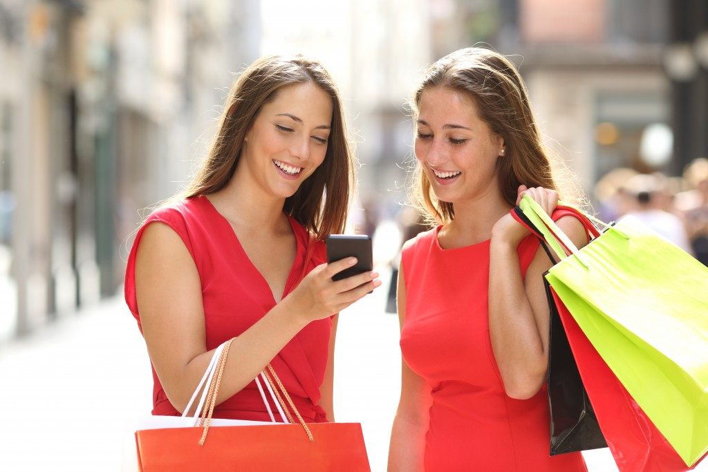 Two girls looking at a phone while shopping