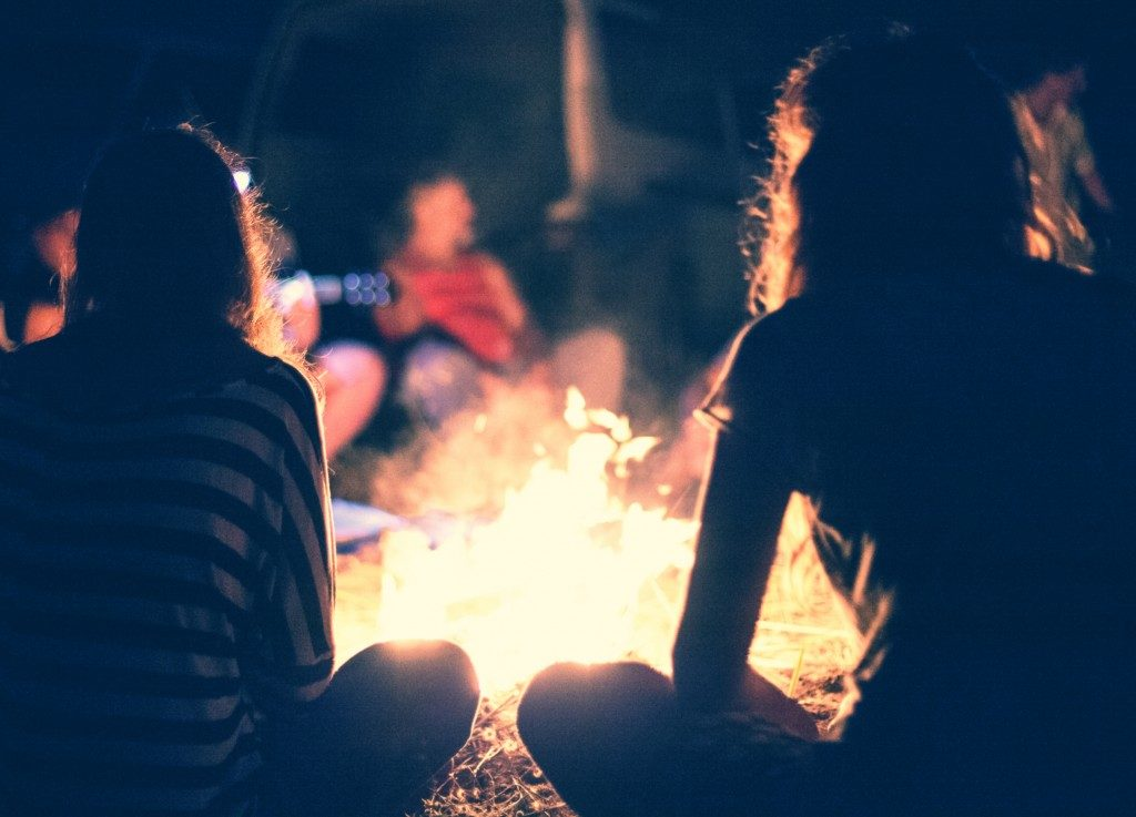 People sitting around a bright bonfire