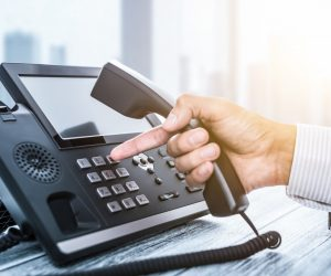 hand of a businessperson dialing on VoIP