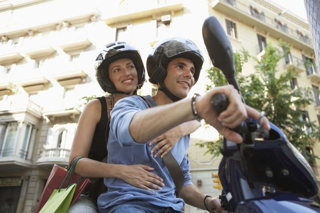 couple smiling while enjoying road trip on scooter